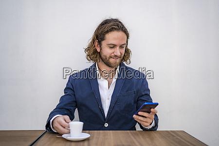 smiling handsome businessman using smart phone