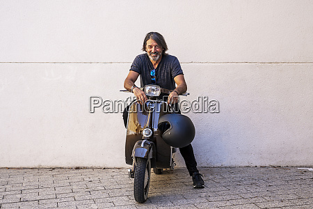 happy man sitting on motor scooter