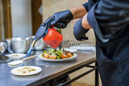 chef preparing dessert with bunsen burner