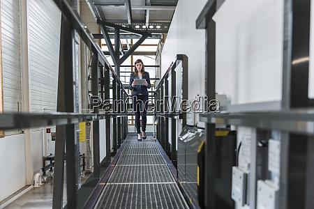 businesswoman using digital tablet while walking