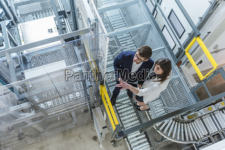 managers discussing while standing in factory
