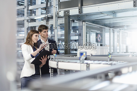 business professionals examining production line in