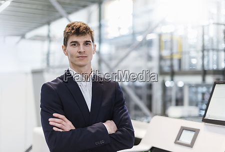 confident businessman with arms crossed standing