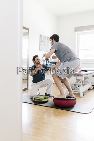 physiotherapist assisting patient practicing on balance