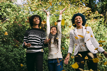 happy children with mother throwing autumn
