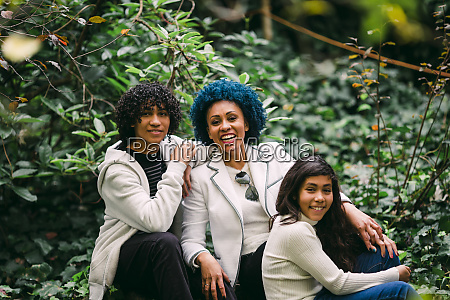smiling mother with children sitting against