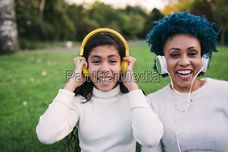 happy mother and daughter listening music