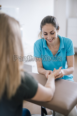 female physiotherapist giving patient a hand