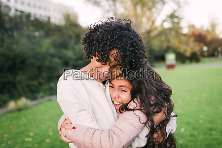 brother embracing cheerful sister while standing