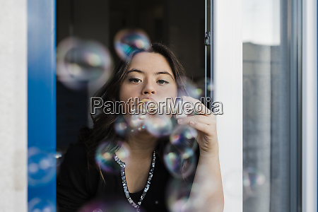 young woman with down syndrome blowing