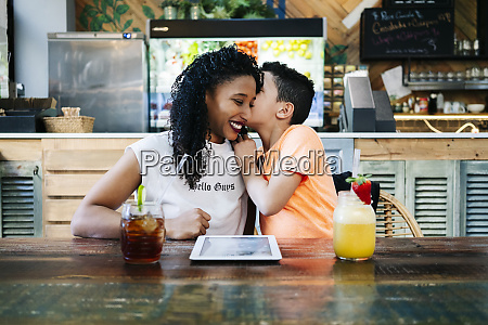 boy whispering in smiling mothers ear