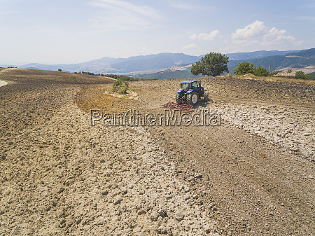 tractor plowing in farm against sky