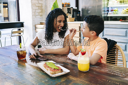 boy feeding happy mother with fork