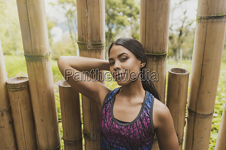 confident young woman standing against bamboos