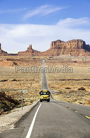 school bus drives on desert road