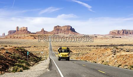 school bus on desert road at