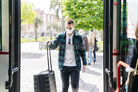 young man wearing protective mask getting