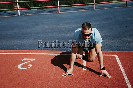 male athlete in starting position on