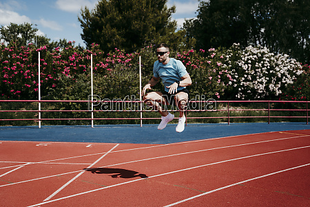 male athlete jumping on tartan track