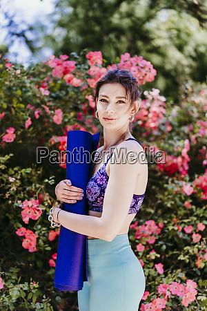 beautiful woman holding yoga mat in