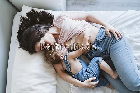 mother breast feeding baby girl on