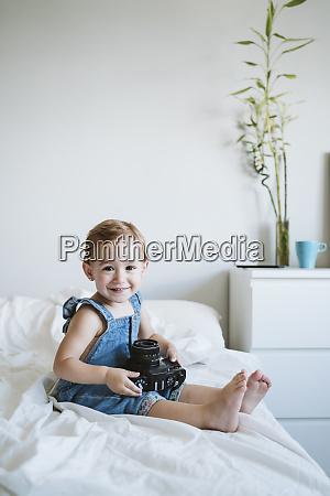 baby girl holding camera at home