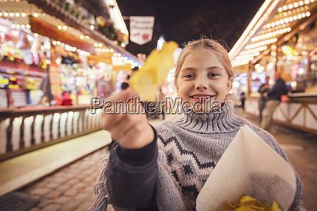 portrait of smiling girl eating potato