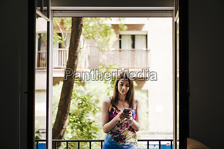 woman using phone while standing in
