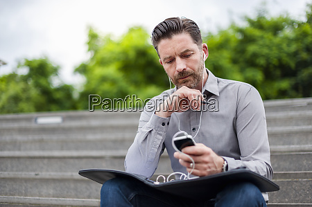 confident businessman using smart phone while