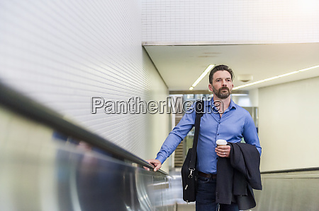 confident handsome businessman standing with disposable