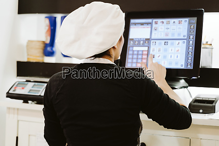 female baker using cash register at
