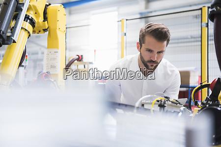 engineer examining robotic arm in factory