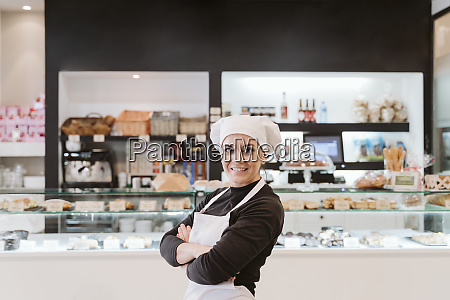 confident female baker standing arms crossed