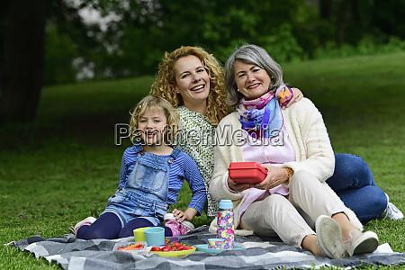 cheerful three generation females enjoying picnic