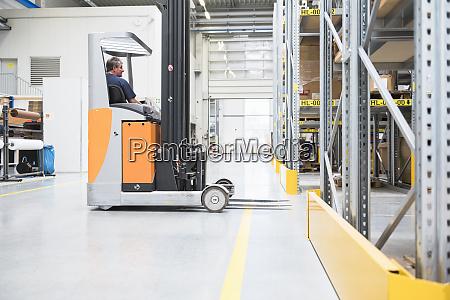 worker on forklift in high rack