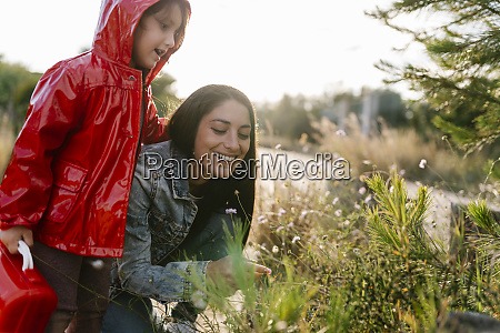 mother and daughter picking wild flowers