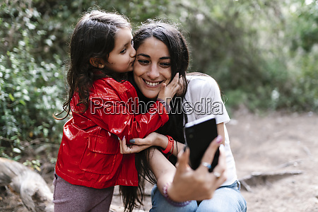 daughter kissing her mother while taking