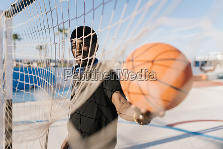 young man holding basketball by net