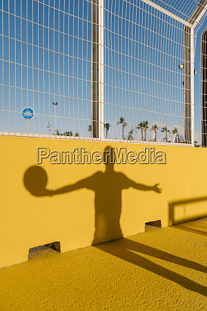 shadow of young man holding basketball