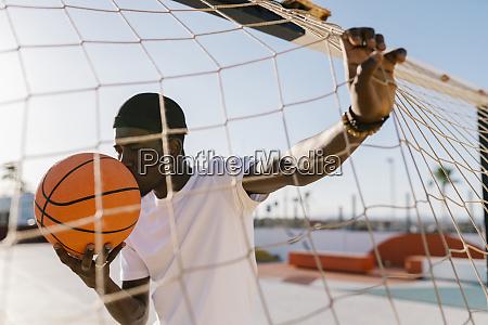 young man kissing basketball while standing