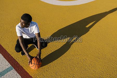 thoughtful young man holding basketball crouching