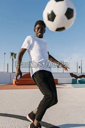 smiling young man playing soccer against