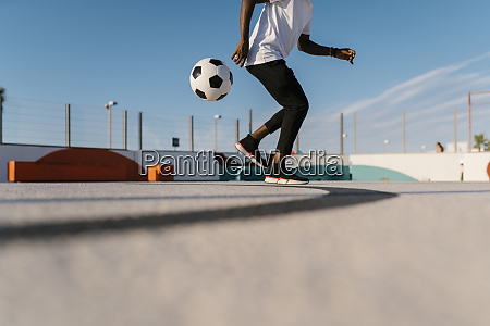 young man juggling with soccer ball