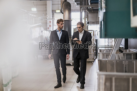two businessmen with tablet walking in