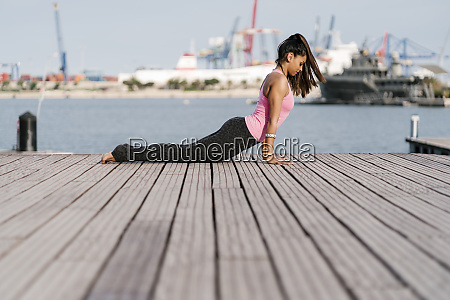 female athlete practicing cobra pose on