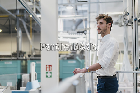 young businessman standing in a factory