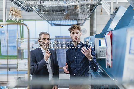 two businessmen discussing in a factory