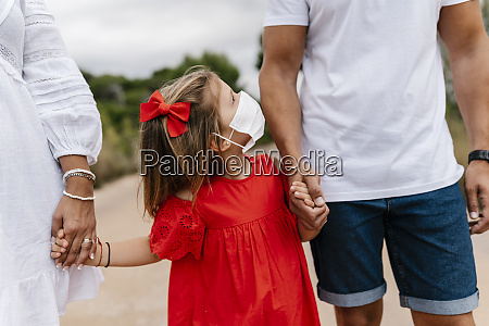 girl wearing mask looking at father