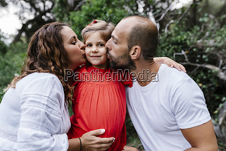 parents kissing girl on cheeks in