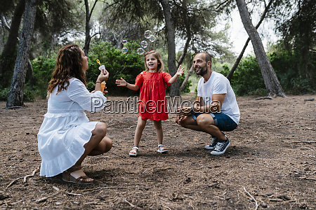 woman blowing bubbles for daughter with